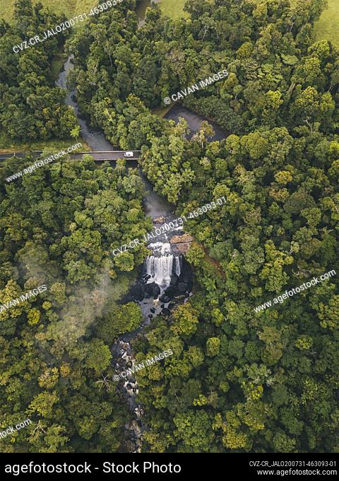 Aerial shot of Zillie Falls sourranded by lush green forest while a van driving through a bridge crossing in Tropical Queensland, Australia
