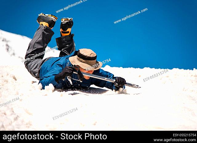 Training to correct slip on a slope or a glacier with the help of an ice ax. A fully equipped backpacker slides on the belly along a snowy slope in the...