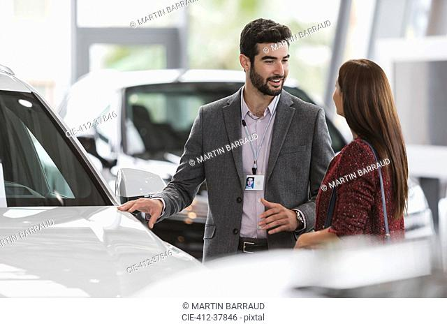 Car salesman showing new car to female customer in car dealership showroom