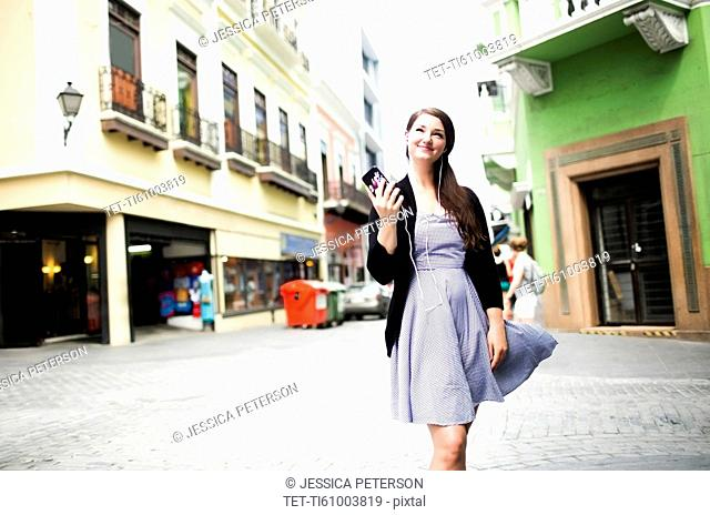 Puerto Rico, San Juan, Woman standing on street and holding smart phone