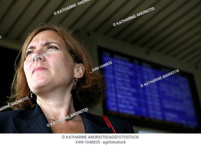 Businesswoman awaits her commuter train standing near platform timetable