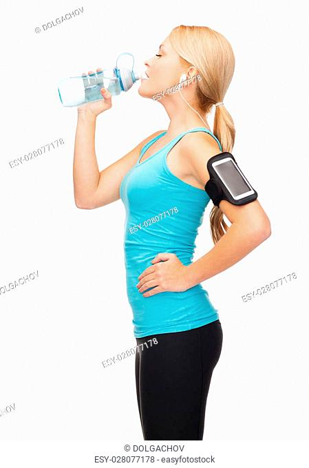 sport, exercise, technology, internet and healthcare - sporty woman listening to music from smartphone with water bottle