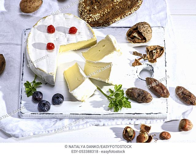 round Camembert cheese on a white wooden board, next to sausage and nuts, white wooden table, top view