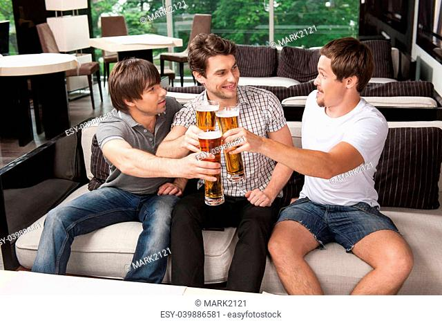 Three male friends drinking cold beer in hot weather. Sitting at the pub