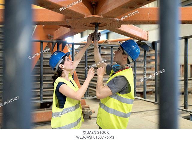 Workers repairing machine in concrete factory