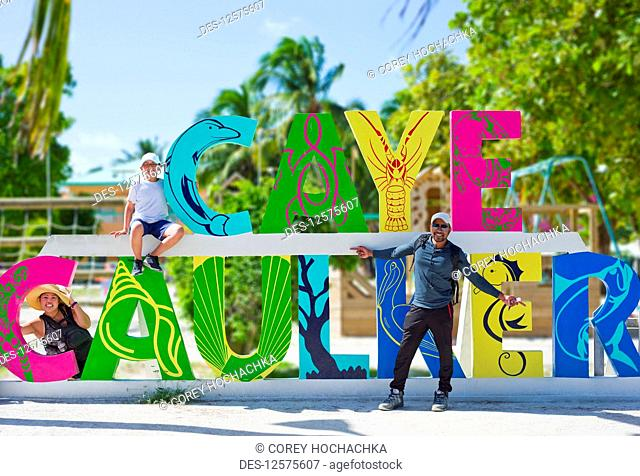 Tourists at the colourful Caye Caulker sign; Belize