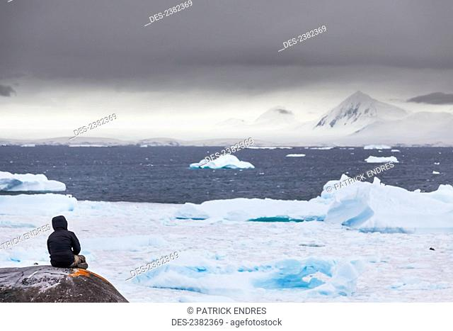 Hiker pauses for reflection on Booth Island, Western Antarctic peninsula; Antarctica
