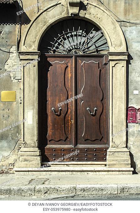 Old typical italian wooden door. Italian house. Ancient house facade. Sunlight. Round door arch. Stone build house. Wrought iron door handles