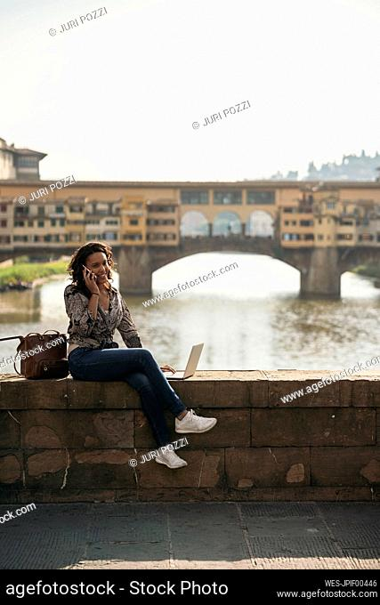 Young woman using laptop and cell phone on a bridge, Florence, Italy