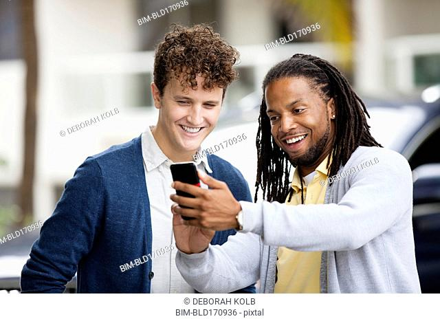 Businessmen using cell phone outdoors