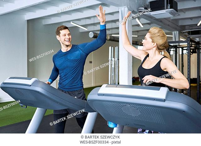Happy man and woman doing high five during treadmill exercise at gym
