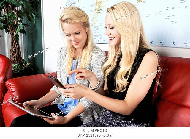 Two beautiful young millennial business women sitting in a workplace on red leather furniture using their handheld devices while waiting for a job interview;...