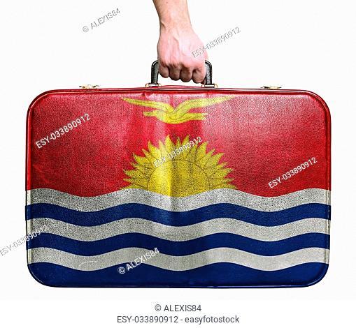 Tourist hand holding vintage leather travel bag with flag of Kiribati