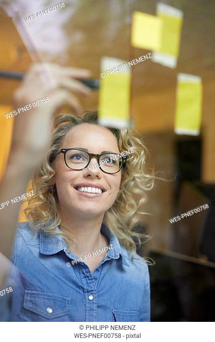 Portrait of smiling blond businesswoman looking at adhesive note on glass pane