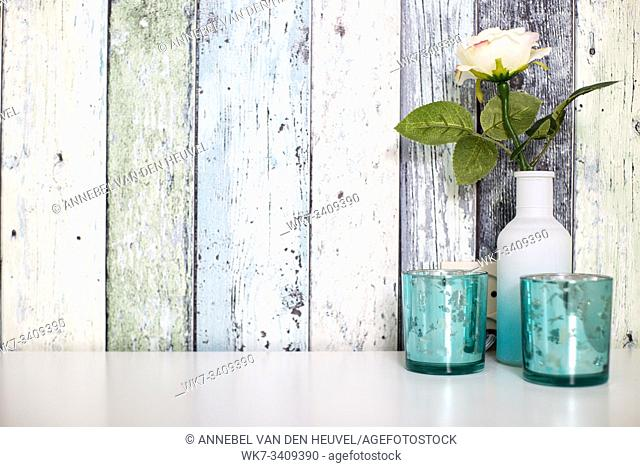 one colorful flower in white vase against wood wall with blue decoration, space for text