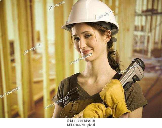 A woman wearing construction hat and holding tool