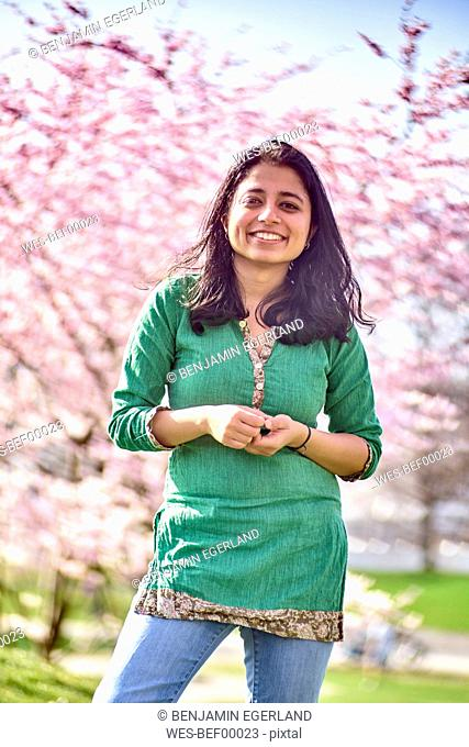 Portrait of happy young woman in a park at cherry blossom tree