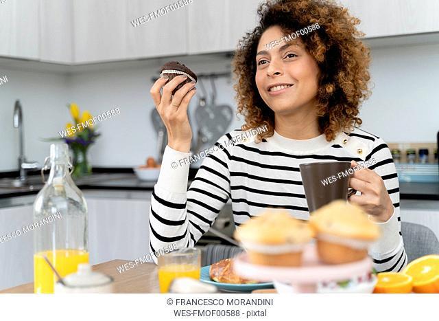 Woman sitting in kitchen, having breakfast