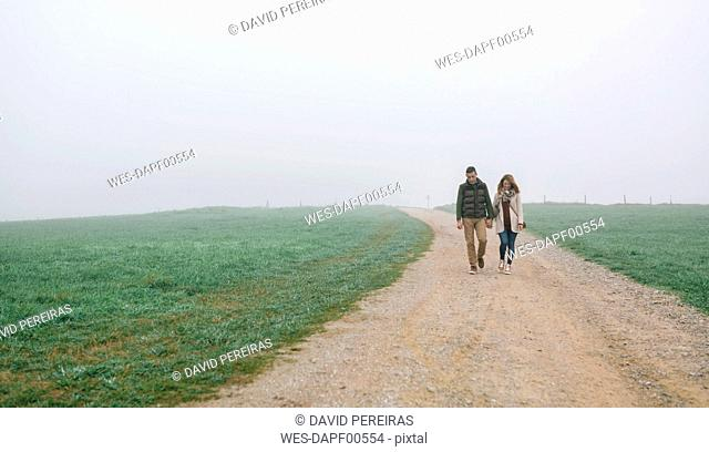 Couple walking on a path on a foggy winter day