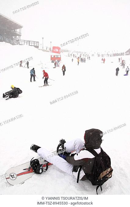 A person putting on their snowboard. Kellaria, Parnassos, Arachova, Viotia, Central Greece, Europe