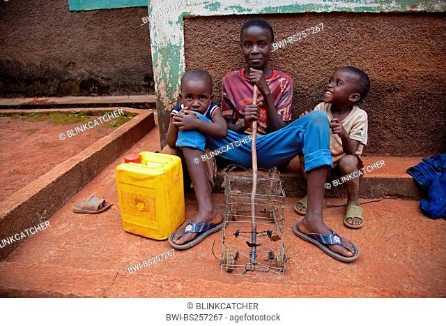 three little children with self-made toy car and water can sitting in front of house wall, Burundi, Gitega