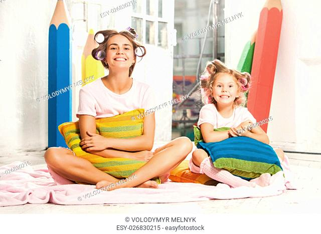 Little smiling girl playing with her mother on white
