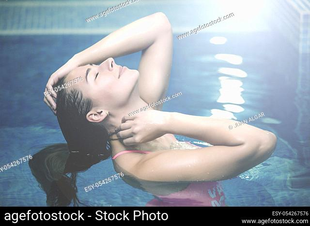 Horizontal indoors shot of young girl with eyes closed adjusting hair and relaxing standing in swimming pool