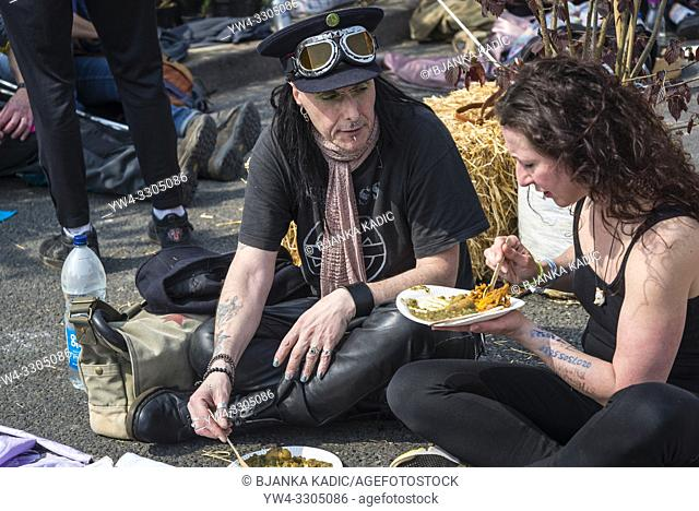 Extinction Rebellion protest on Waterloo Bridge, Punks eating, London, UK