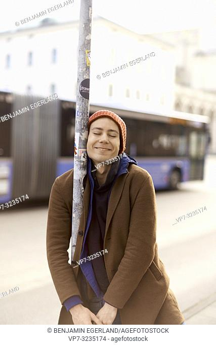 happy young androgynous man relaxing at street post, in city Munich, Germany
