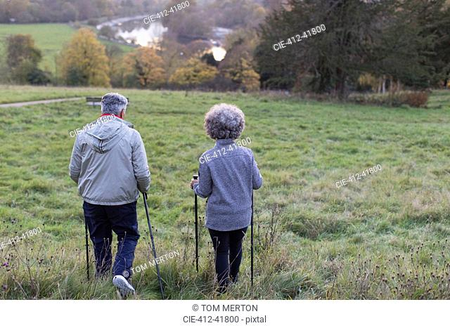 Active senior couple hiking with poles in rural field