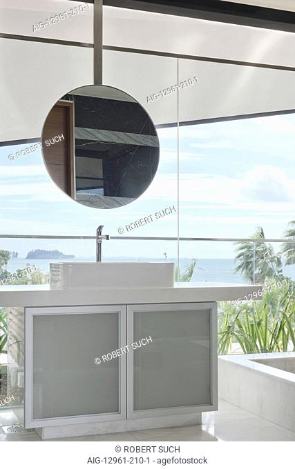 Modern bathroom with round mirror and view from picture windows
