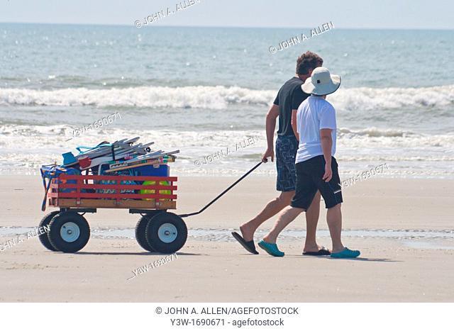 Couple pulls loaded cart along beach on Isle of Plams South Carolina USA