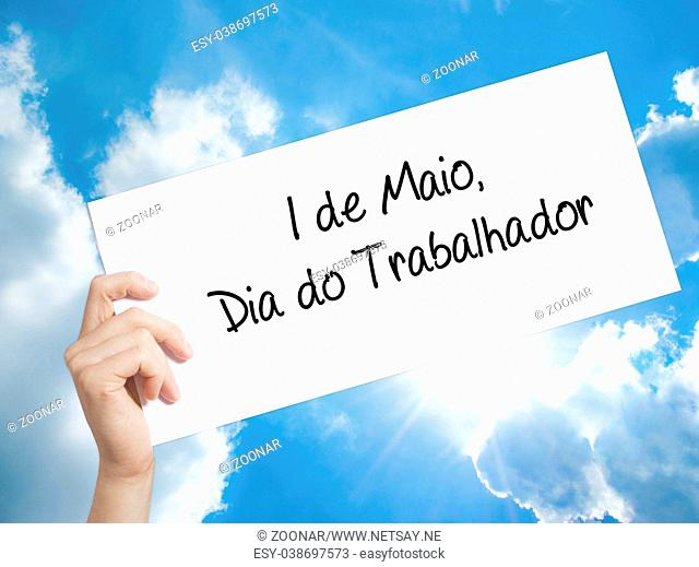 1 de Maio, Dia do Trabalhador (In Portuguese: 1 May, Labor Day) Sign on white paper. Man Hand Holding Paper with text. Isolated on sky background