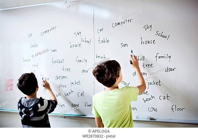 Rear view of boys writing on whiteboard in classroom