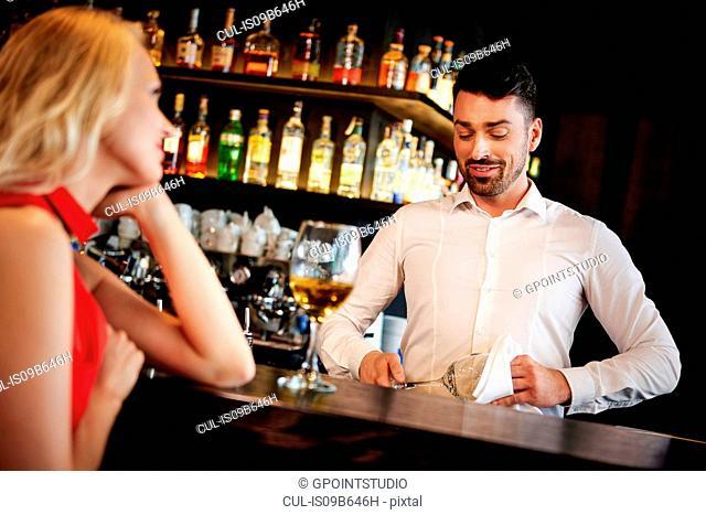 Barman flirting with young woman sitting at bar