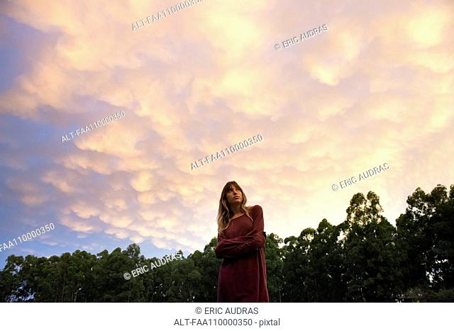 Young woman outdoors at twilight, looking up in thought