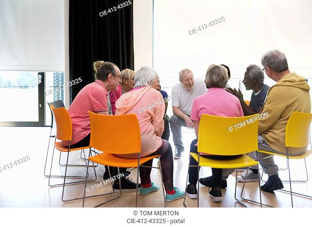 Active seniors talking in circle in community center