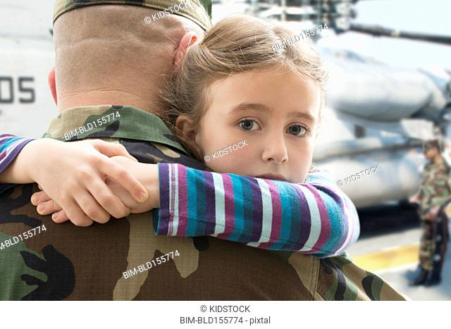 Caucasian returning soldier hugging daughter near helicopter