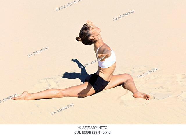 Side view of woman on beach doing the splits, arms open in yoga position