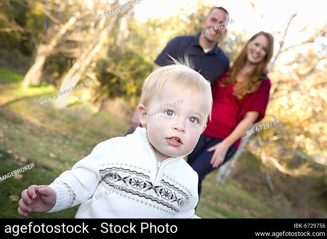 Cute young boy walking in the park as adoring parents look on from behind