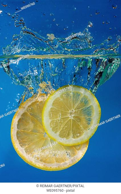 Lemon and grapefruit slices splashing into water with a blue background