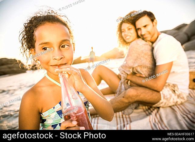 Girl with her family having a soft drink at sunset at the beach
