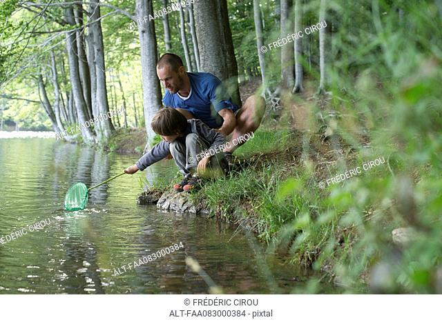 Father and son crouching at water's edge with fishing net