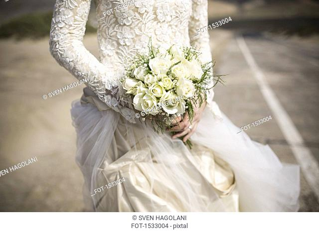 Midsection of bridge holding rose bouquet outdoors