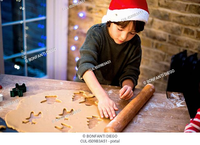 Boy in Santa hat preparing Christmas cookies at kitchen counter