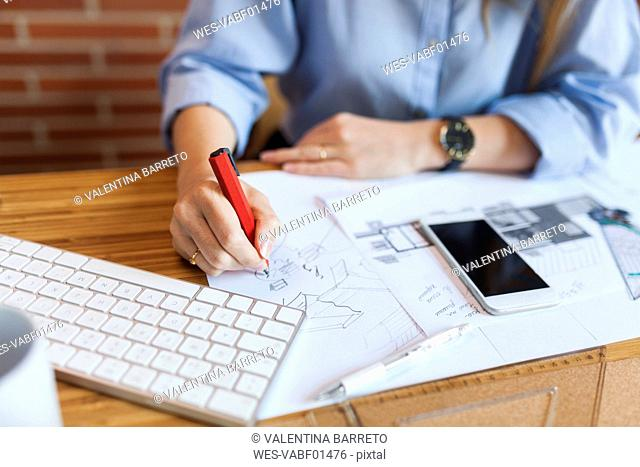 Young woman working in architecture office, drawing blueprints