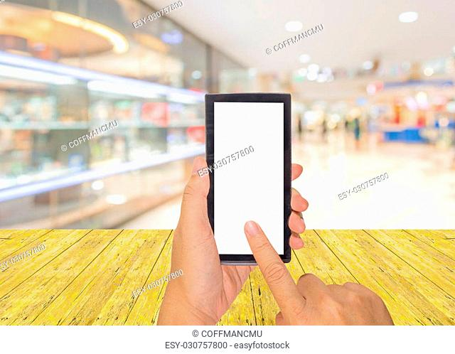 male hand is holding a modern touch screen phone and Abstract background of shopping mall and people, shallow depth of focus
