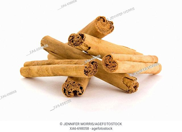 Six cinnamon sticks are piled together to form a triangle
