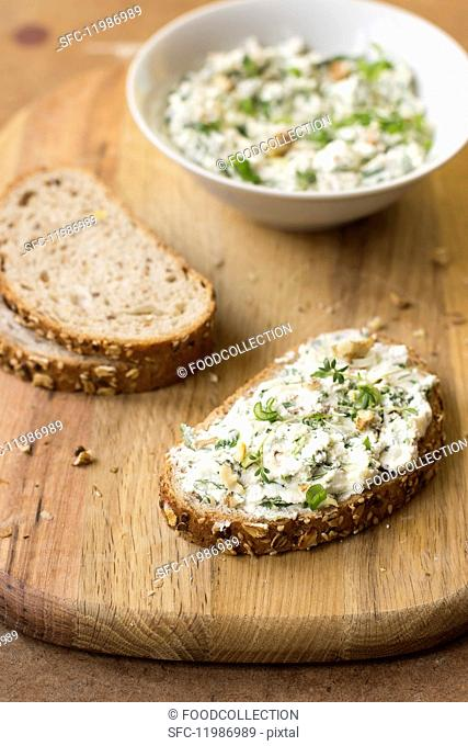 A slice of bread with goats' cheese, spring onion, dandelion greens, thyme and walnuts