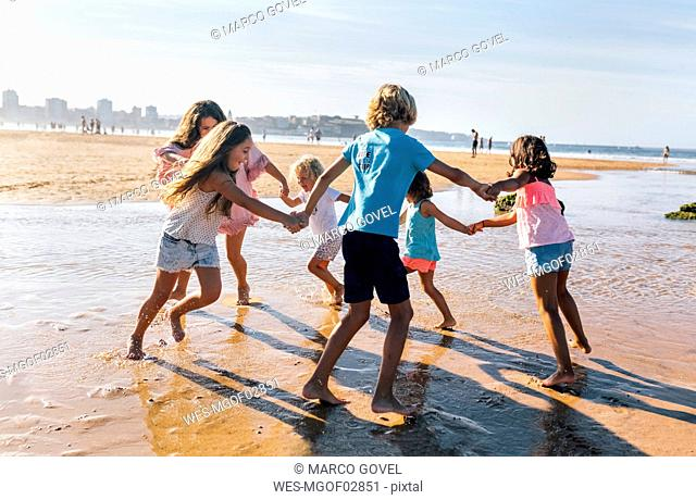 Group of six children playing ring-a-ring-a-roses on the beach